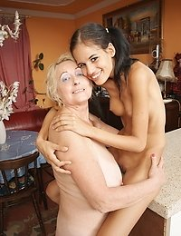 Hot babe fisting a mature lesbian on the counter